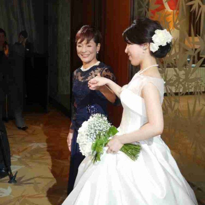 晴れやかな笑顔とフォーマルドレス姿でお嬢様のご結婚式を迎えるお母様